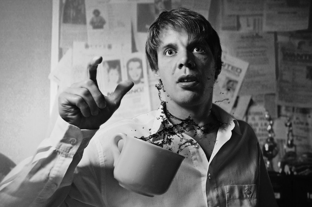 Man dropping a mug of coffee in shock